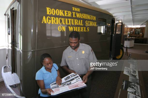 A man and woman by the Booker T Washington School bus in the George Washington Carver Museum