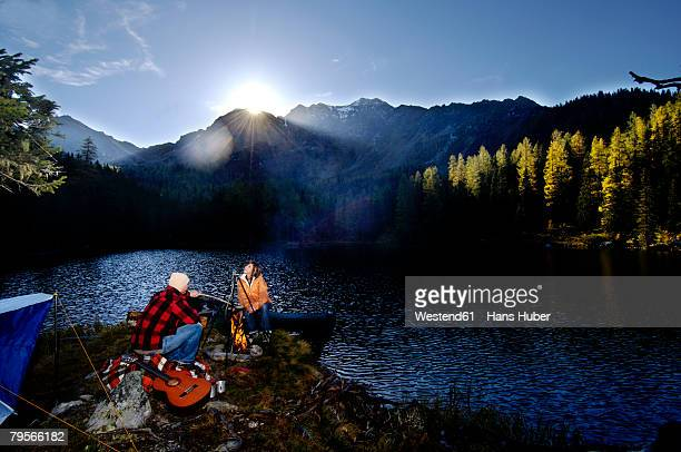 man and woman camping at lake - utomhuseld bildbanksfoton och bilder