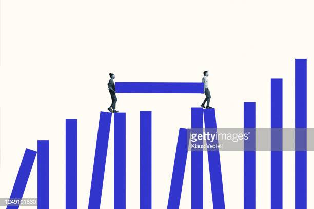 man and woman carrying blue bar on graph - バイアス ストックフォトと画像