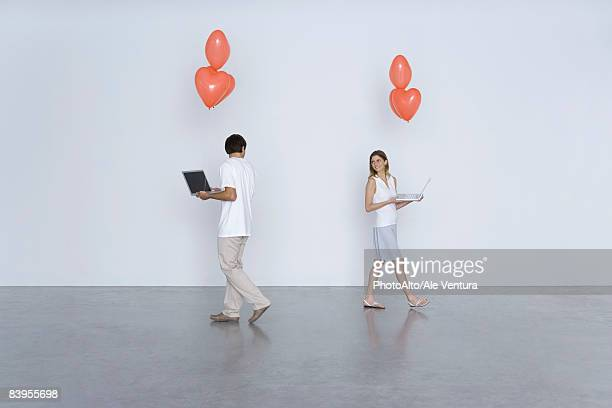 Man and woman carrying laptop computers and heart balloons, smiling over their shoulders at each other
