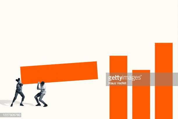 man and woman carrying large orange bar graph - バイアス ストックフォトと画像