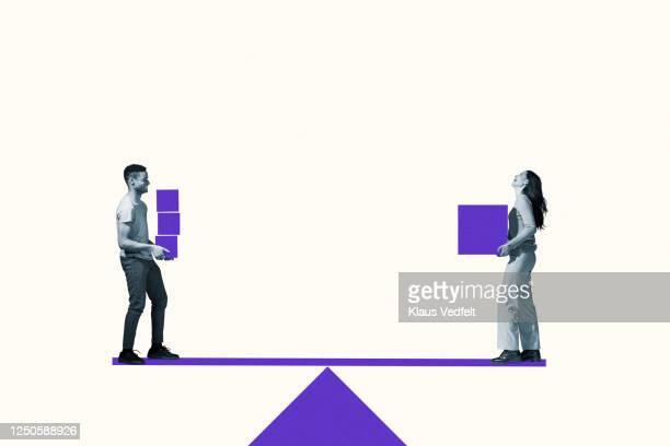 man and woman carrying purple blocks on seesaw - equality stock pictures, royalty-free photos & images