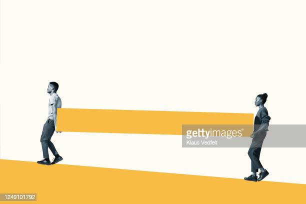 man and woman carrying yellow slab - teamwork stock pictures, royalty-free photos & images