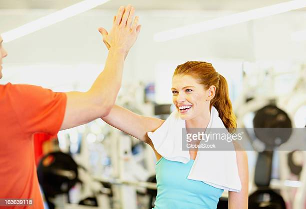 Man and woman celebrating success at gym