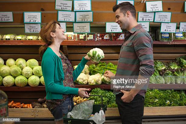 man and woman chatting whilst shopping in health food store - produce aisle stock photos and pictures