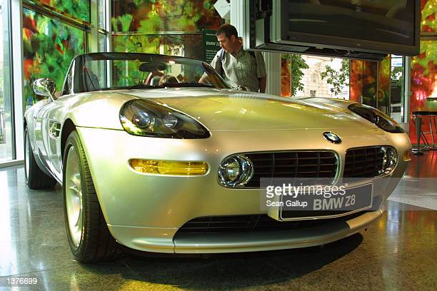 A man and woman check out a BMW Z8 convertible at the BMW Pavillion September 9 2002 in Munich Germany According to new economic data released...