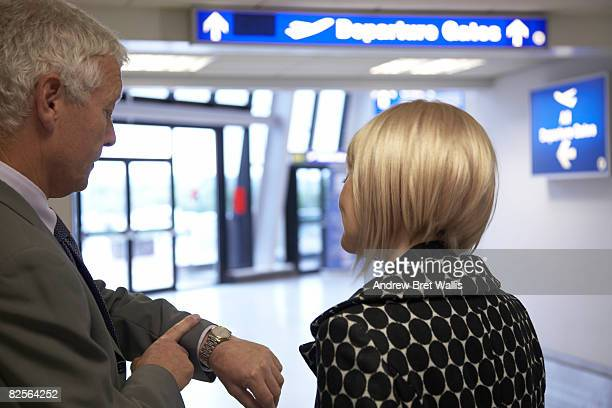 man and woman checking time at the airport