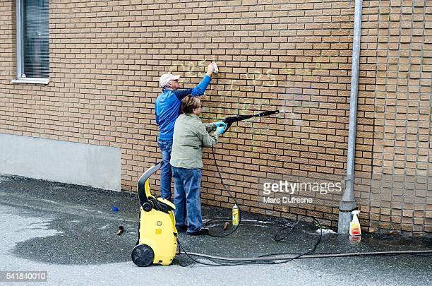 Homme et Femme de nettoyage graffiti sur le mur de briques