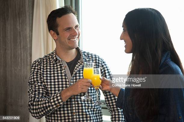 Man and woman clinking glasses