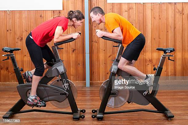 Man and woman competing against each other on exercise bikes