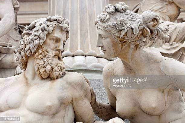 man and woman conversing the atena statue in vienna, austria - statue stock pictures, royalty-free photos & images
