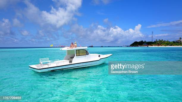 man and woman couple relaxing sunbathing together on private luxury boat in maldives - schiffstaxi stock-fotos und bilder