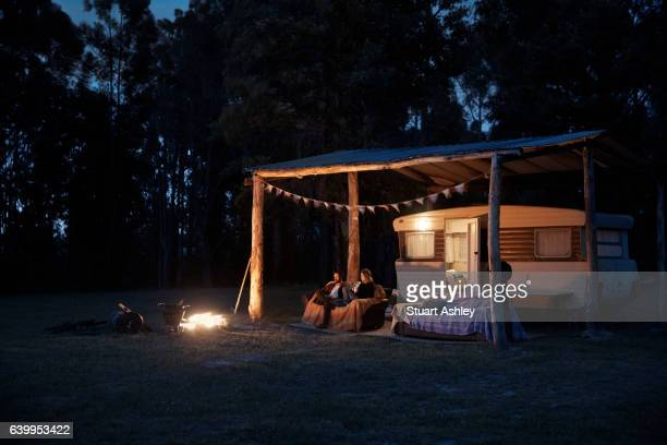 Man and woman couple sitting by caravan and fire at night