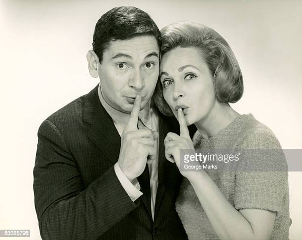 Man and woman covering lips with pointer