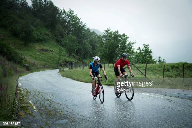 man and woman cycling down mountain road in norway - wielrennen stockfoto's en -beelden