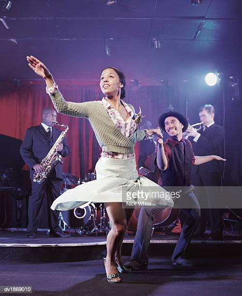 Man and Woman Dancing in a Nightclub and a Jazz Band on Stage in the Background