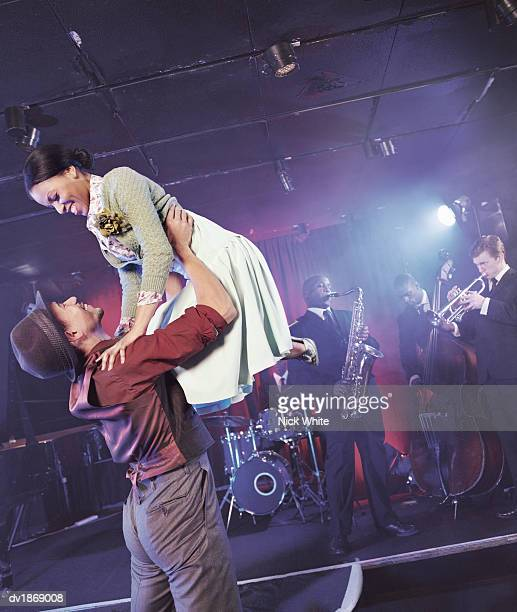 Man and Woman Dancing in a Nightclub, Man Lifting Woman Mid-air, and a Jazz Band on Stage in the Background