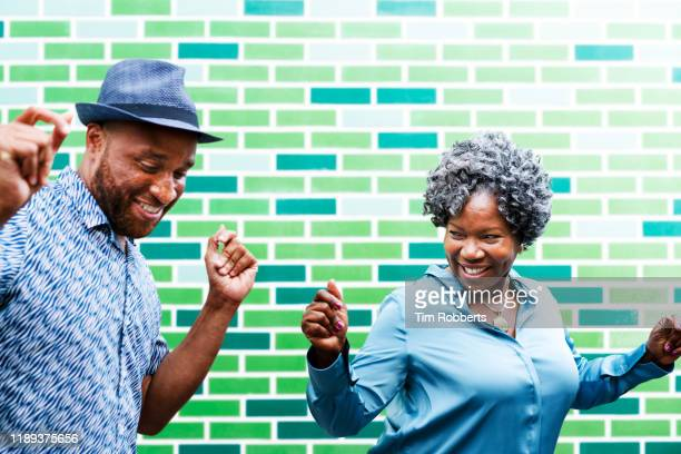 man and woman dancing next to wall - mature adult stock pictures, royalty-free photos & images