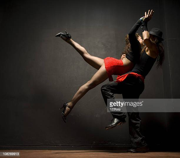 man and woman dancing tango on black background - ballroom dancing stock pictures, royalty-free photos & images
