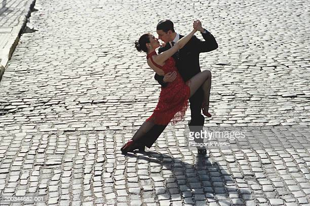 Man and woman dancing tango on cobblestone road, elevated view