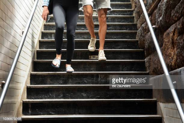 man and woman descending stairs at a subway station in midtown Manhattan