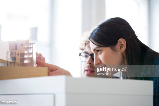 Man and woman discussing architectural model in office
