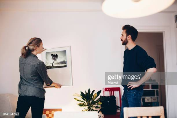man and woman discussing painting at home - couple fighting stockfoto's en -beelden