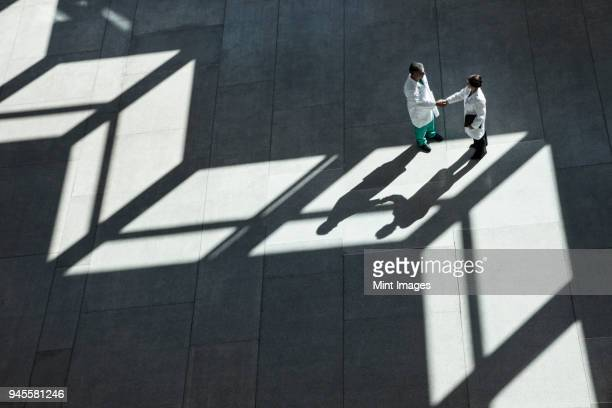 man and woman doctors conferring over medical records in a hospital lobby. - medical building stock pictures, royalty-free photos & images
