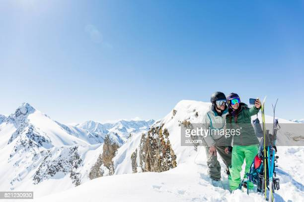 Man and woman doing a selfie photograph at mountain top during backcountry skiing day