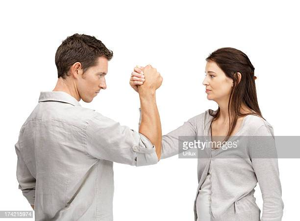 man and woman doing arm wrestling showing their displeasure - female wrestling holds stockfoto's en -beelden