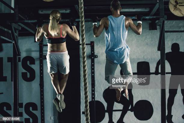 Man and woman doing chin-ups together