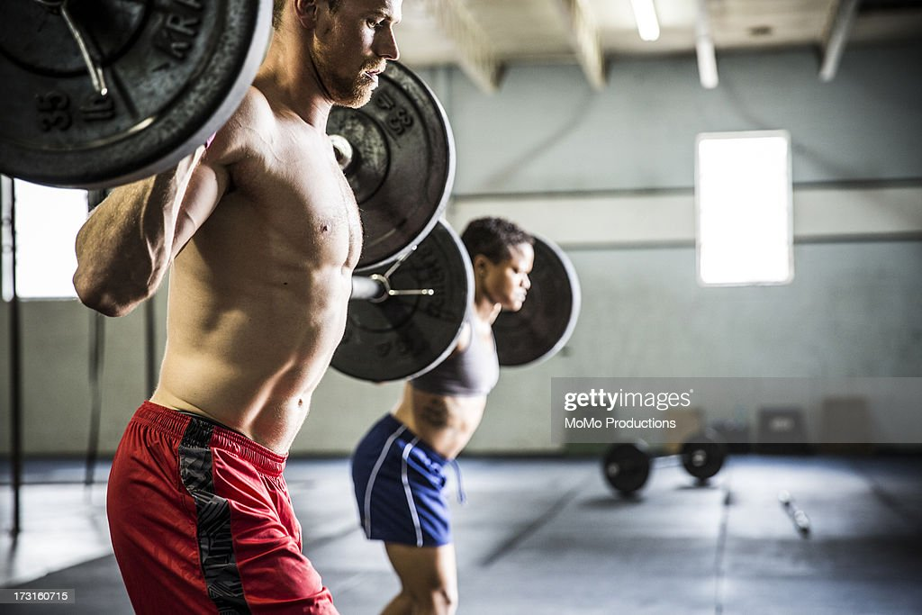 man and woman doing gym lunges : Stock Photo