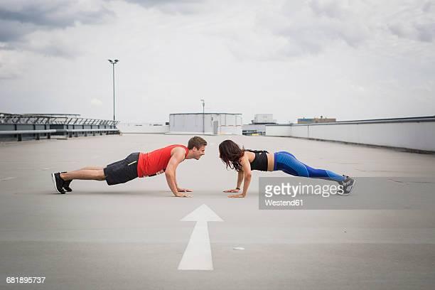 Man and woman doing push ups outdoor