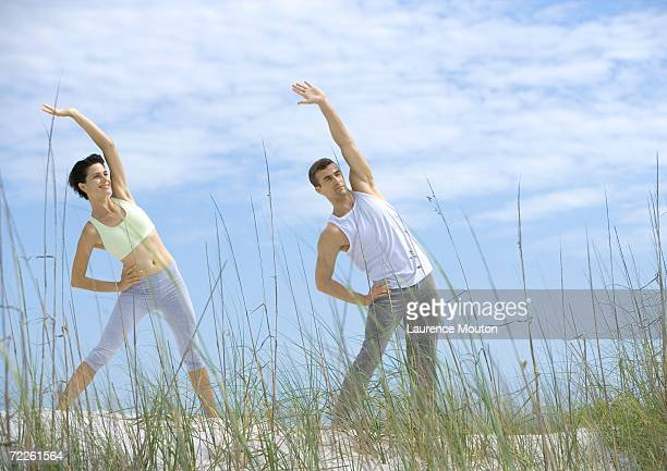 man and woman doing side stretches on beach - arms akimbo stock pictures, royalty-free photos & images