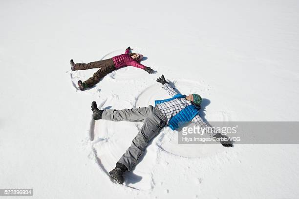 Man and woman doing snow angel