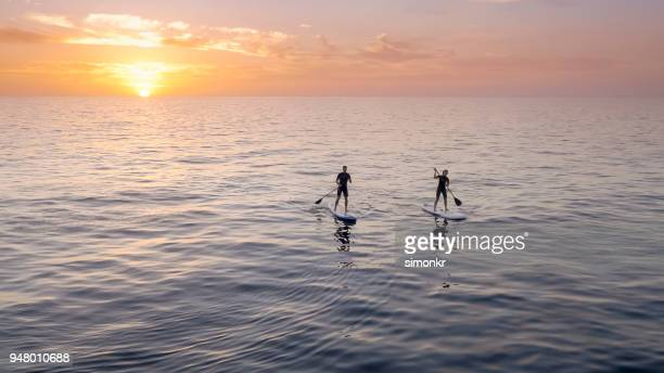 Man and woman doing standup paddling in sea