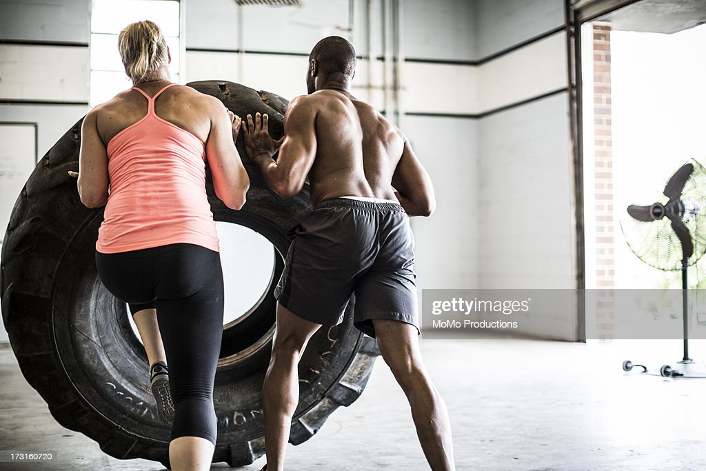 man and woman doing tire-flip exercise