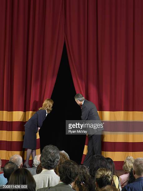 man and woman drawing back curtains on stage, audience in foreground - bending over in skirt stock pictures, royalty-free photos & images