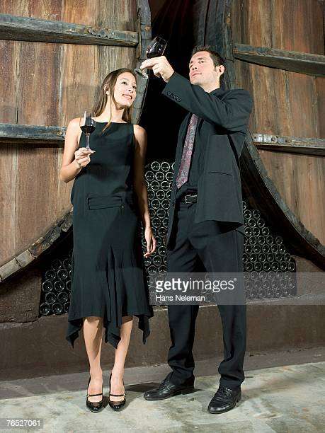 Man and woman dressed nicely, standing in front of wine barrels