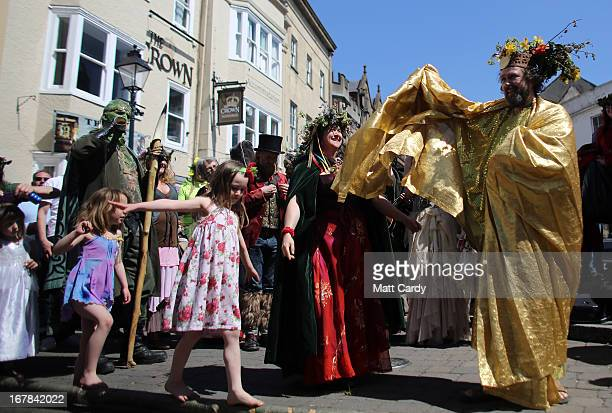 A man and woman dressed to represent the May King and Queen dance as they take part in a Beltane May Day celebration in Glastonbury main street on...