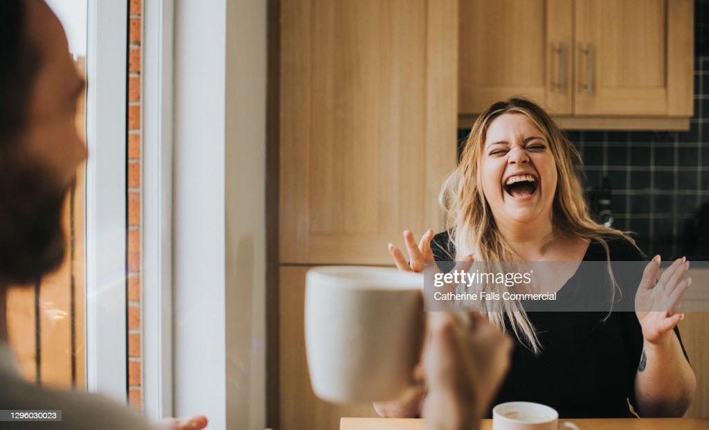 Man and Woman drink coffee / tea together as woman laughs hysterically : ストックフォト