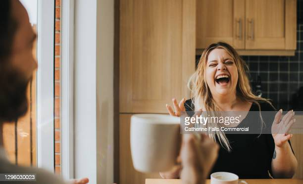 man and woman drink coffee / tea together as woman laughs hysterically - hysteria stock pictures, royalty-free photos & images