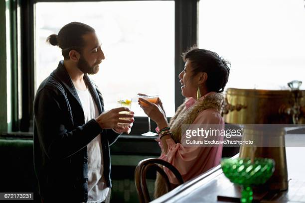 man and woman drinking and socialising in recreational bar - heshphoto stock pictures, royalty-free photos & images