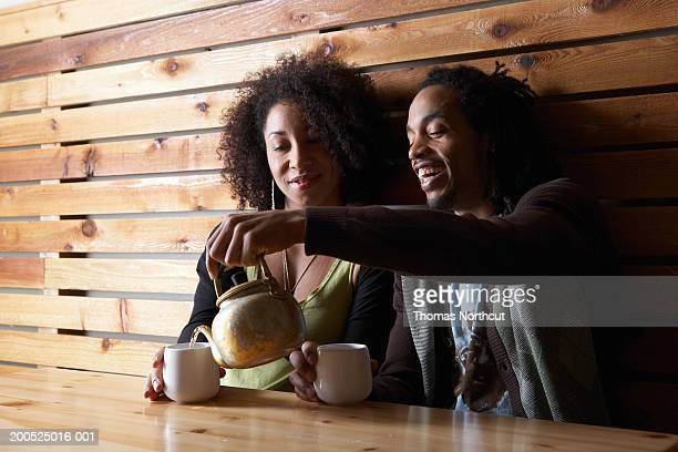 man and woman drinking tea at table in cafe, smiling - social grace stock pictures, royalty-free photos & images