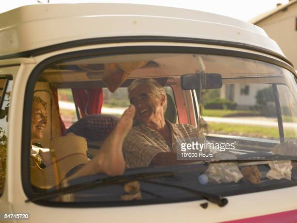 Man and woman driving a camper van, laughing