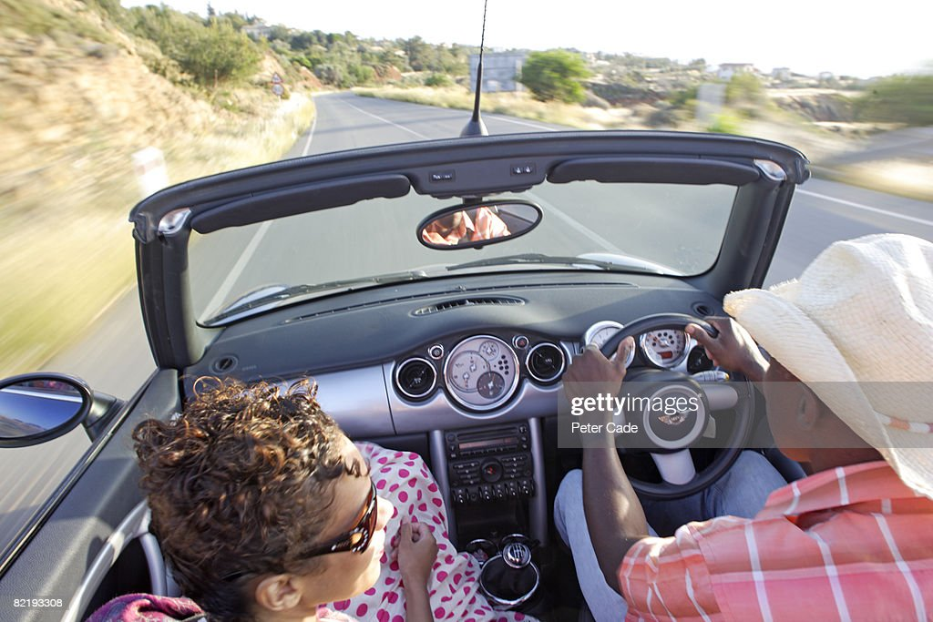 Man and woman driving in car with roof down : Stock Photo
