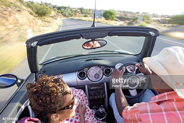 Man and woman driving in car with roof down