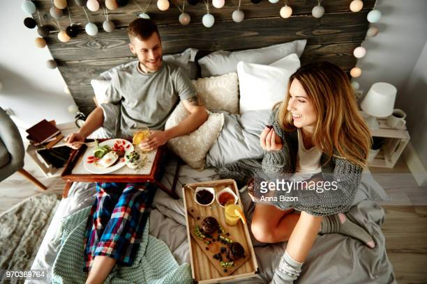 man and woman eating breakfast on bed. debica, poland - lazy poland stock photos and pictures