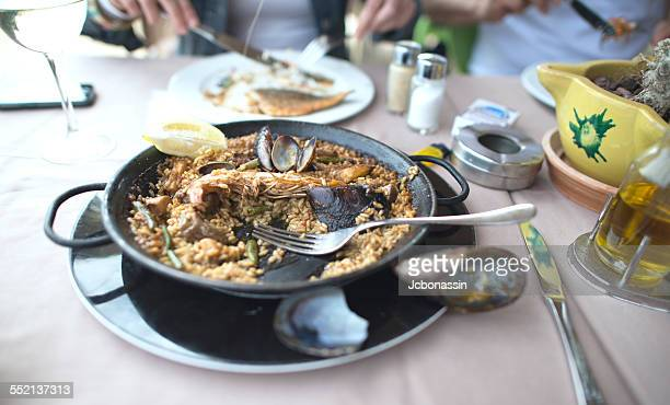 man and woman eating paella - jcbonassin stock pictures, royalty-free photos & images