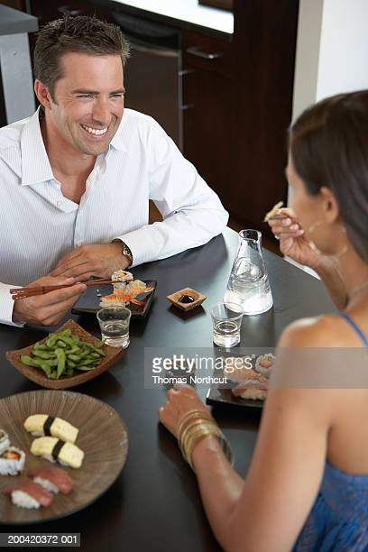 Man and woman eating sushi, smiling at one another (focus on man)